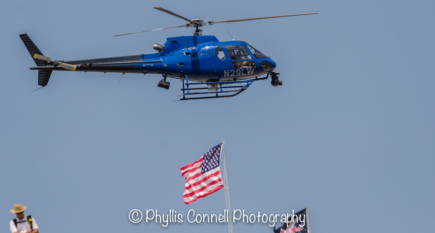Helicopter flying above American Flag.